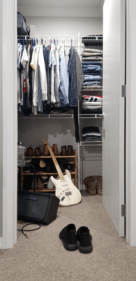 view from outside a closet door looking in on clothes, shoes, and a guitar