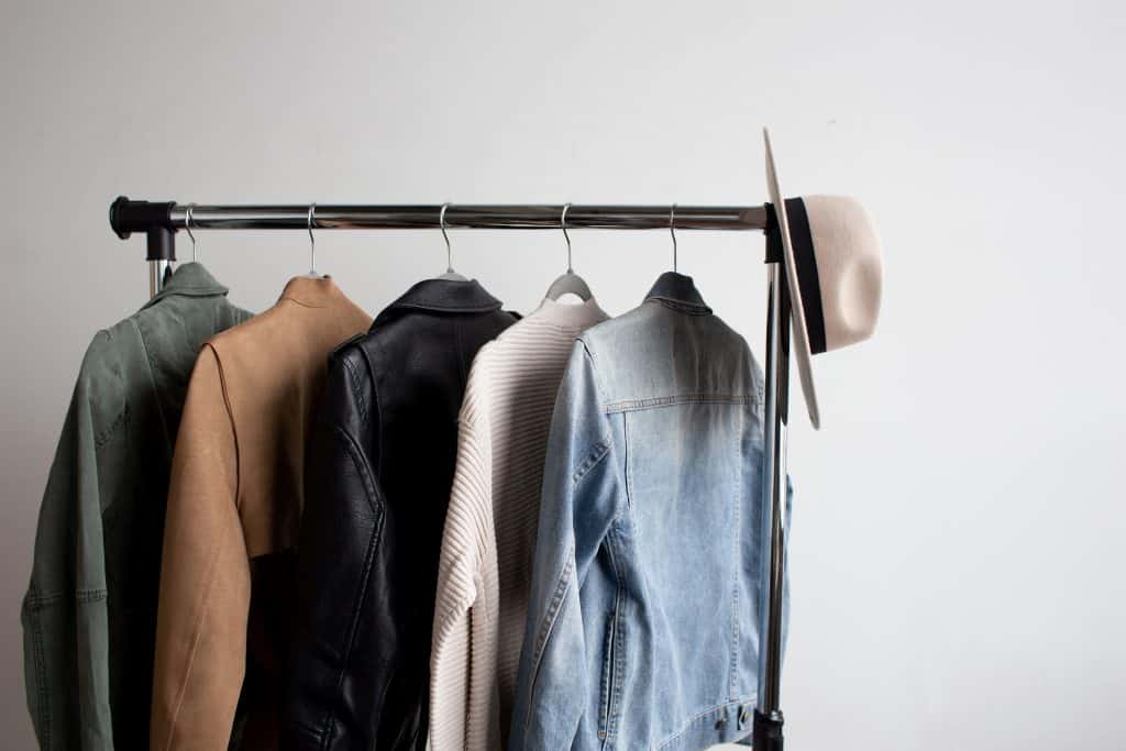 Five neutral clothing pieces on a clothing rack with a sunhat hanging on one end.