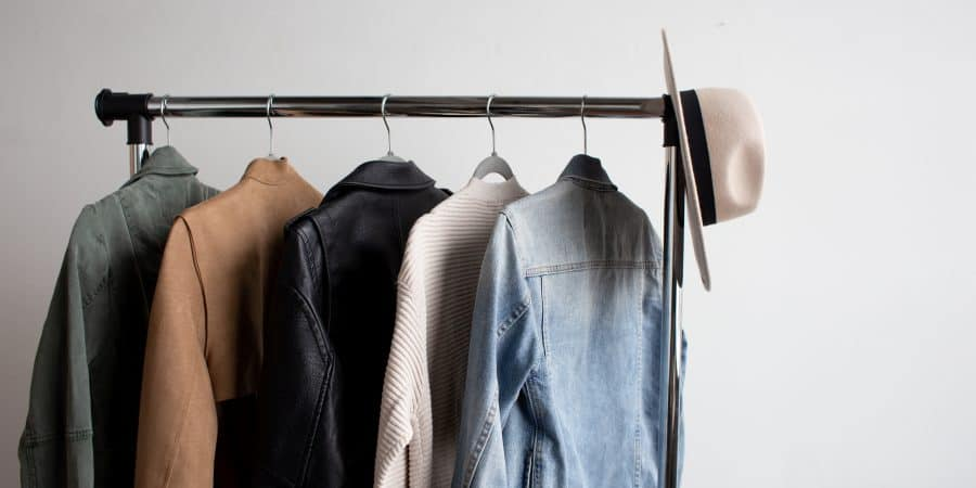 five clothing items hanging on a clothes rack