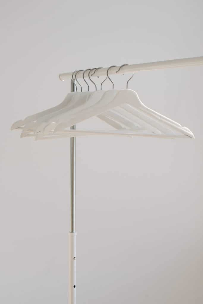 clothes rack with seven empty white hangers