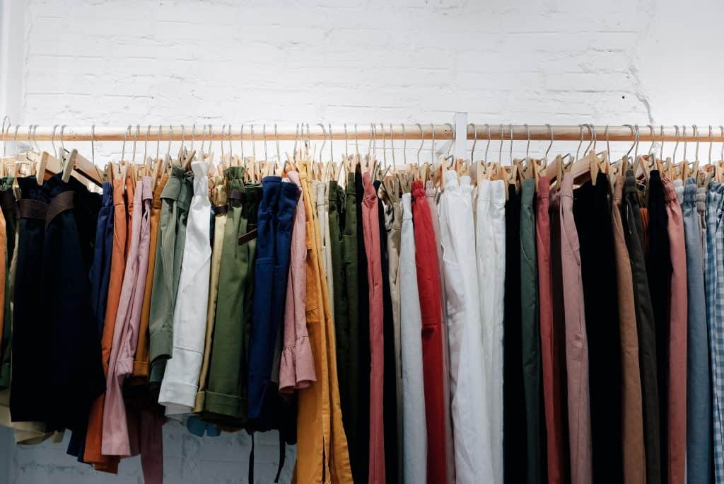 row of colorful clothes hanging on a long clothes rack