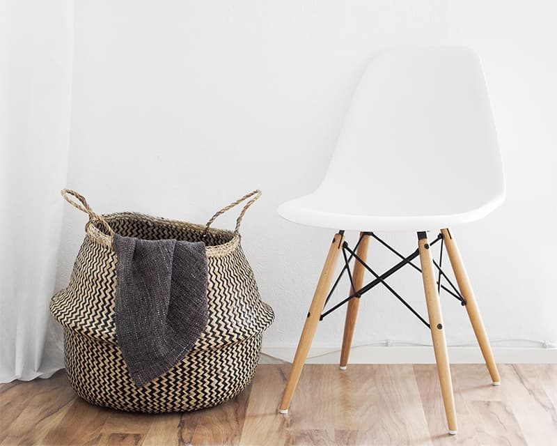 minimalistic photo of a white chair next to a woven basket with a piece of cloth hanging along the side.