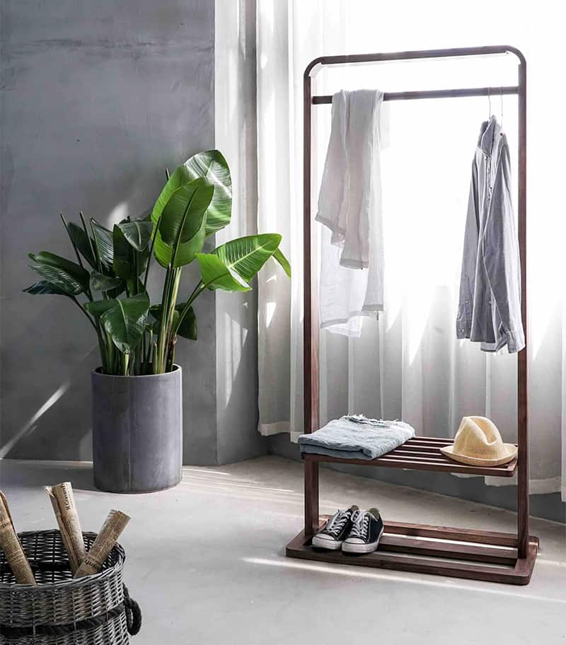 Minimalistic view of a clothes rack with one outfit, in front of a sunny window.