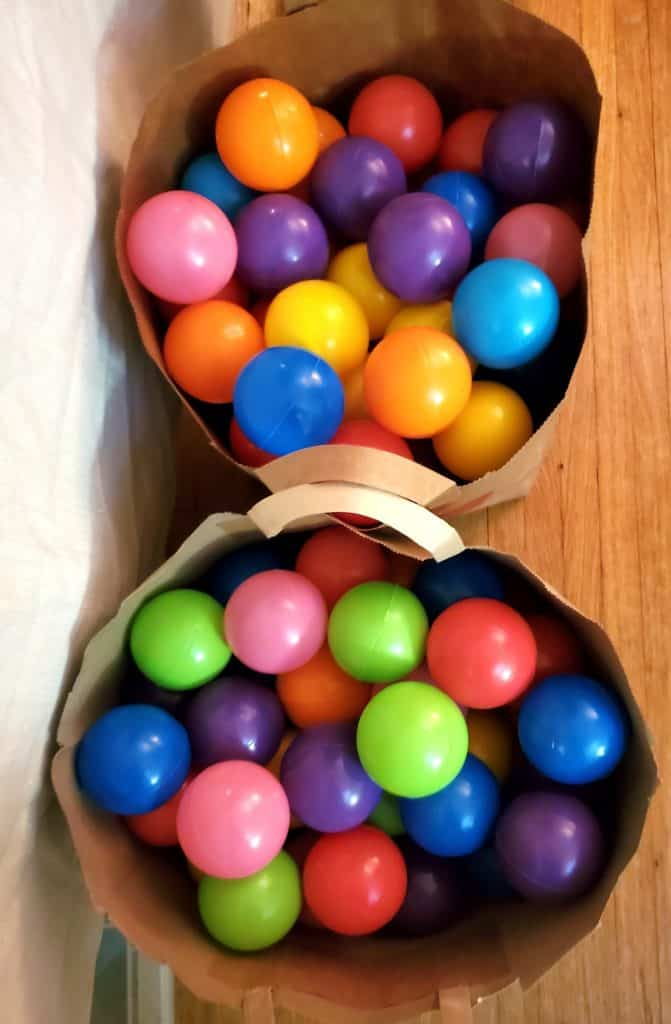 Two brown paper bags filled with colorful play balls.